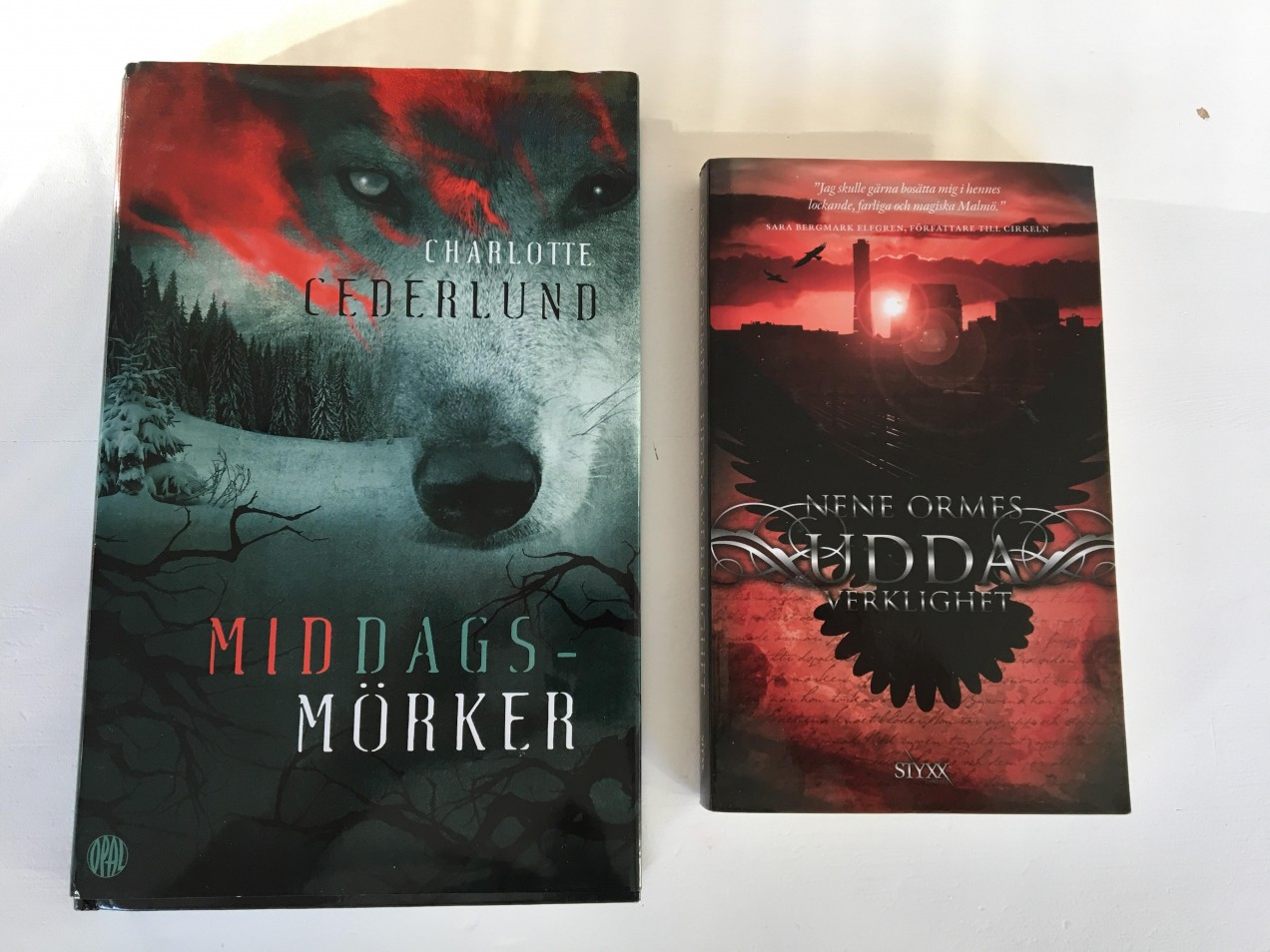 """Jämförelse. Charlotte Cederlunds """"Middagsmörker"""" och Nene Ormes """"Udda Verklighet"""". Båda med omslag av Anna Henriksson/Pixelpiraya"""